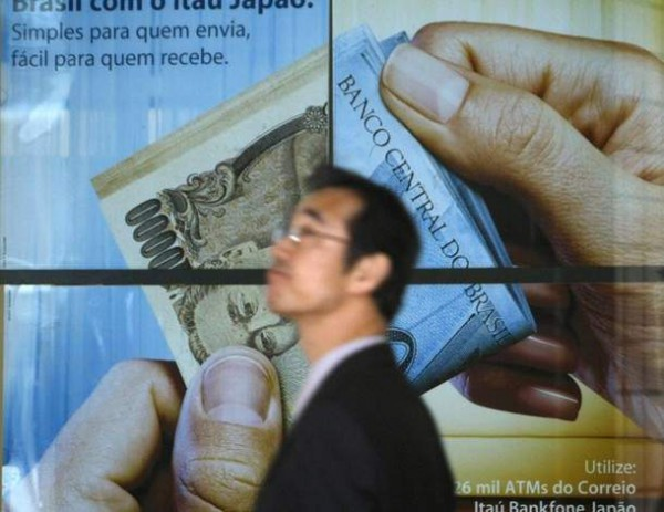 A man walks past a poster of a bank at a business district in Tokyo